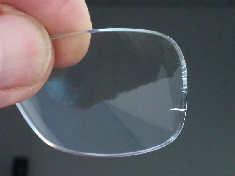 Polycarbonate eyeglass lens with many edge cracks forming from reaction to Windex glass cleaner